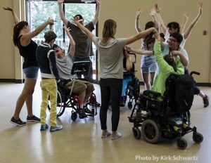 Photo of 11 adults in a circle, with everyone reaching one or two arms up above their heads. Some are holding hands. Three people are using wheelchairs and eight people are standing.