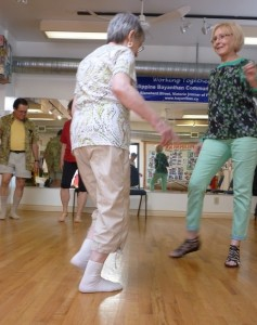 Photo: four seniors dancing, in twos facing each other, lifting up one foot
