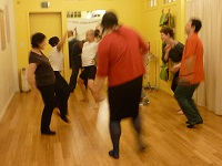 Photo: four people in a circle smiling dancing, and two people facing each other arms in the air