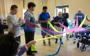 Photo: group of people each holding a strip of fabric attached to a circle in the middle