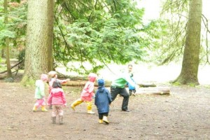 Photo: six children and one adult running in the forest