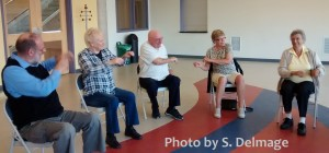Photo: 5 seniors sitting down all moving theirs arms at the same time
