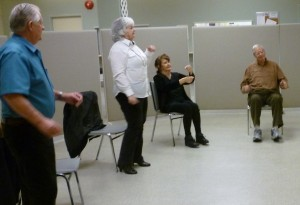 Photo of 4 seniors dancing moving their arms; 2 standing, 2 sitting