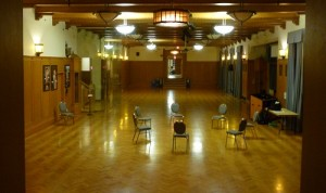 Photo: a very large conference room or hall, with a shiny floor and 7 chairs in a circle