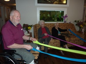 Photo: three older adults holding arms of a dance prop, plus a cat sitting on the couch.