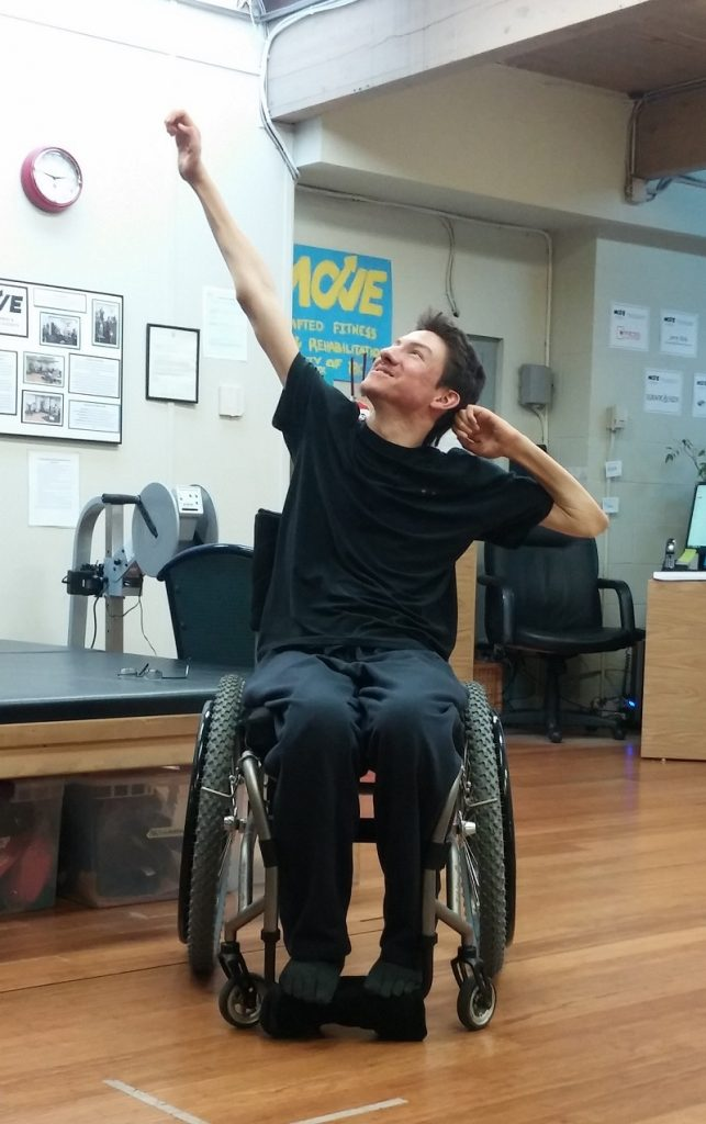 Kristian is turning his head and looking up to the top left corner of the photo, with a smile. He has one arm diagonally up to the left and his other elbow is out to the right with his hand by his ear. He is wearing a black t-shirt and dark pants and is seated in his manual wheelchair. There is some gym equipment in the background.