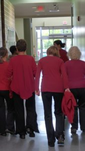 Photo of 6 people's backs, going down a hallway, most wearing red tops