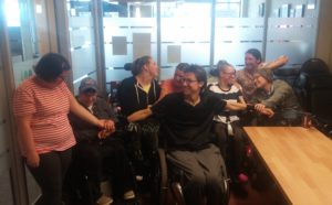 Photo of 8 people smiling at each other and holding each other's hands, arms and shoulders. Most are seated.