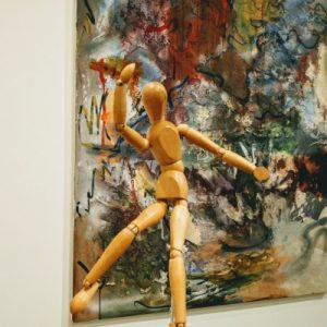 Photo of a marionette-type of figurine with an arm raised and arm out, in front of a mixed media painting with varied colours and textures.