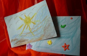 drawings of a sun, birds and shoreline, and under sea creatures