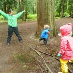 Photo: one adult and three children with arms wide, wearing rain gear in forest