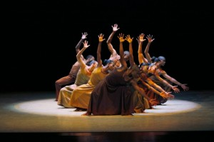 Photo: a dozen dancers squatting leaning left with right arms raised