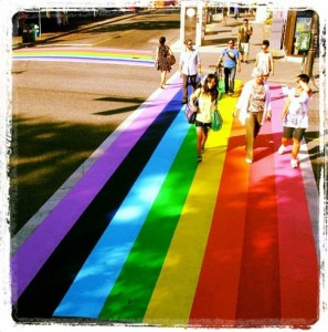 Photo of a rainbow crosswalk and 7 people crossing the street towards the camera