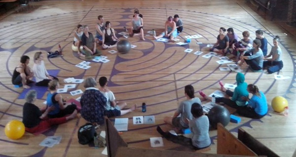 Photo of 20 people sitting in circle in pairs with hands on backs