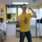 Photo: one dancer wearing sunglasses with elbows bent and smiling