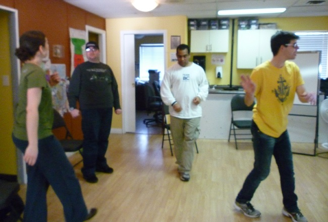 Photo: four adults dancing in a room with wood floors