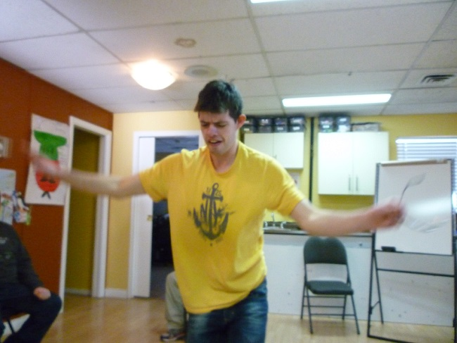 Photo: a man dancing facing the camera with both arms out to the sides, elbows slightly bent, and looking downward