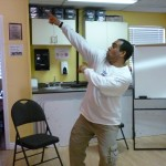 Photo: a man dancing looking to the right with right arm straight raised diagonally with index finger pointing, and left elbow bent across his body