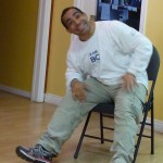 Photo: a man sitting down leaning over his right leg with a big smile to the camera