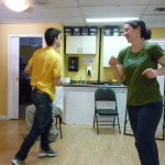 Photo: two people moving quickly in a circle - a man wearing a yellow shirt and a woman wearing a green shirt and smiling