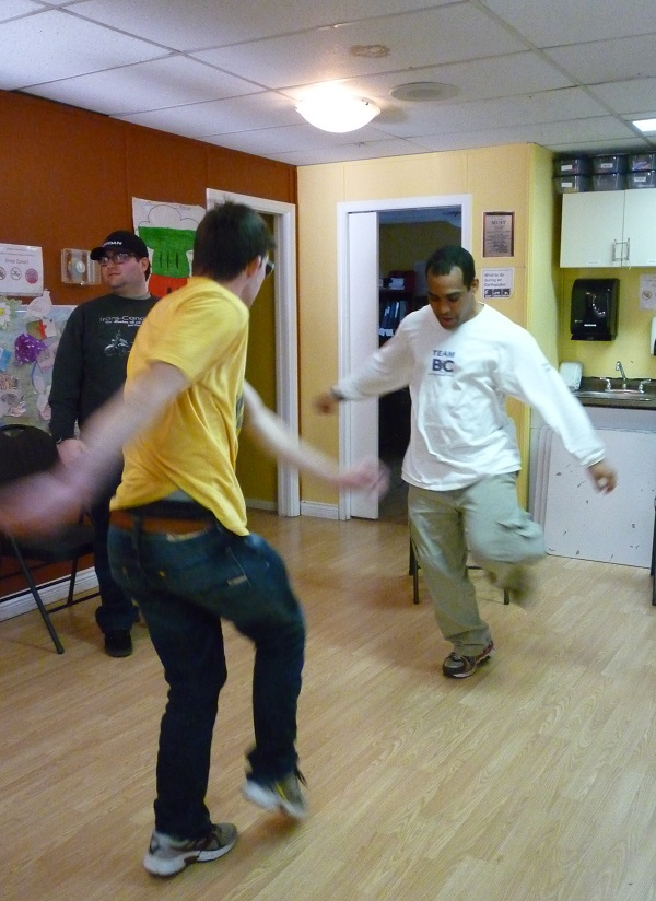 Photo: two men dancing facing each other with one leg lifted and arms out to the sides; another man in the background looking to his right