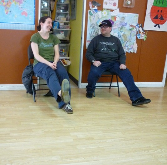 Photo: a woman and a man sitting, each with one heel out to the front, smiling