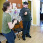Photo: two adults standing up with an elbow bent holding eggshakers