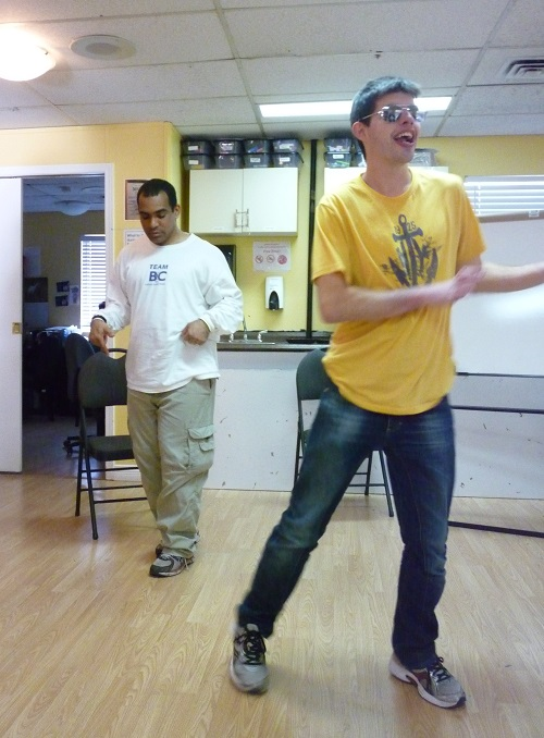 Photo: two men dancing, stepping a foot and arms with elbows bent