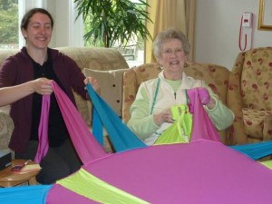 Photo: two women smiling in front of a pink circular dance prop, each holding two prop arms.