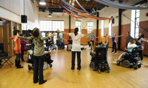 18 adults are in a big circle in a dance studio. Some dancers have their arms stretched wide open to their sides and some dancers have their arms raised to the front with elbows bent. 8 people are seated, using a variety of styles of wheelchairs, and 10 people are standing.