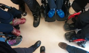 The feet of nine adult dancers are in a circle. They are wearing a variety of sizes and types of casual shoes, boots, socks with a cloud pattern, and running shoes. 5 people have just one shoe visible pointing to the middle, and 3 people have both their feet resting on the foot rests of their wheelchairs.