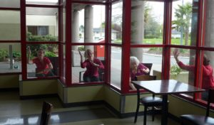 Photo of four dancers making shapes with arms while seated outside each framed by a red window frame.