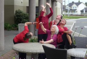 Photo of five dancers on a patio, all wearing red tops and looking up to the sky, each making a different shape