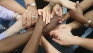 Photo of seven people holding each other's hands across the middle of the circle