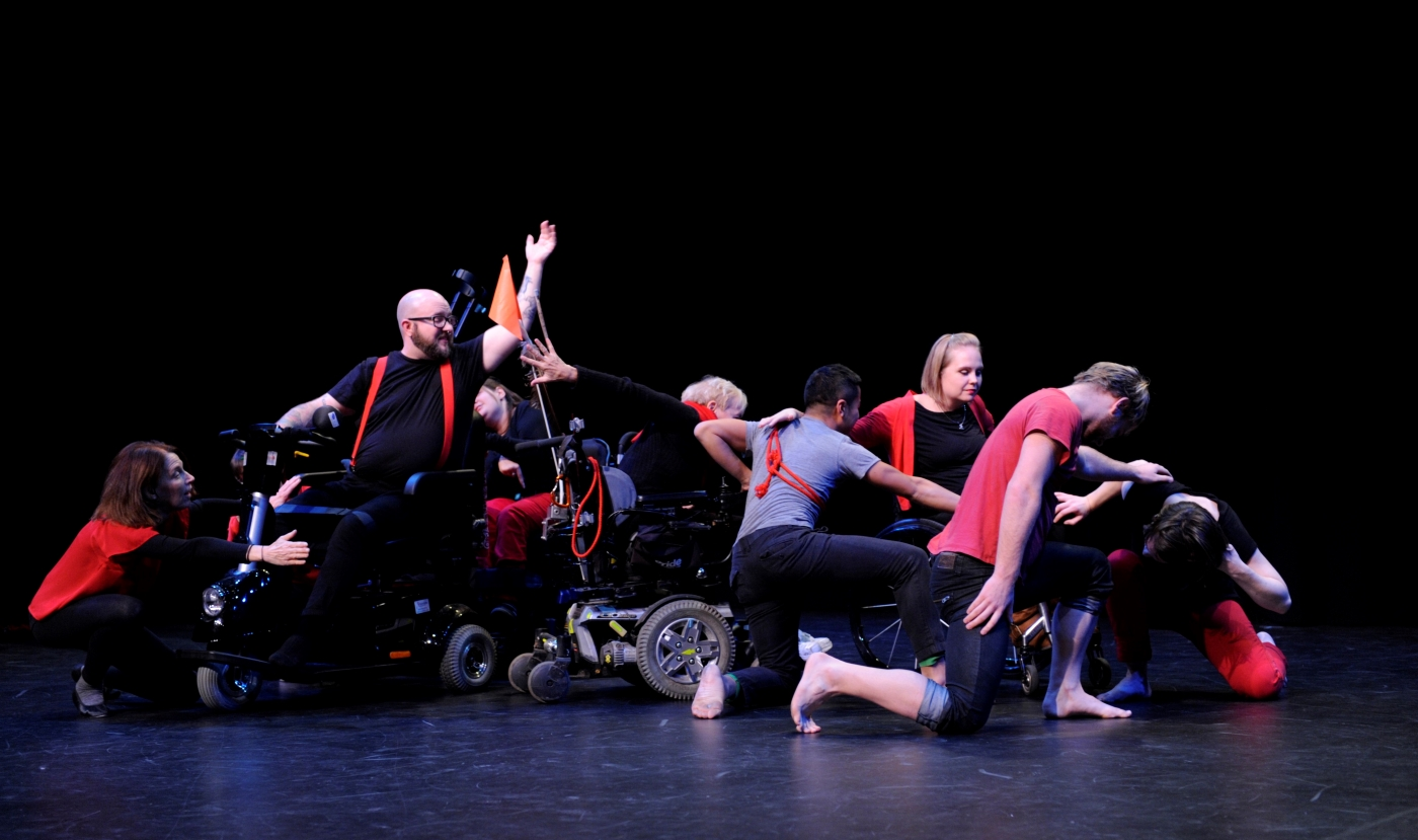 Photo of 9 dancers connecting different ways on stage, some are seated and some are kneeling