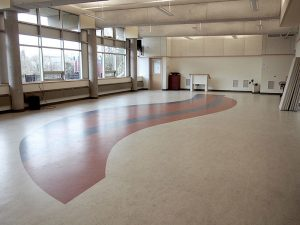 Photo of a large room with large windows and a wavy red design on the floor
