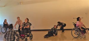 Seven dancers are spread out in a studio. Most are pushing their hands downward and looking up to the ceiling.